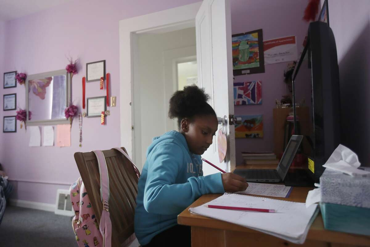 Sunnyside Elementary School fourth-grader Miriam Amacker does school work in her room at her family's home in San Francisco.