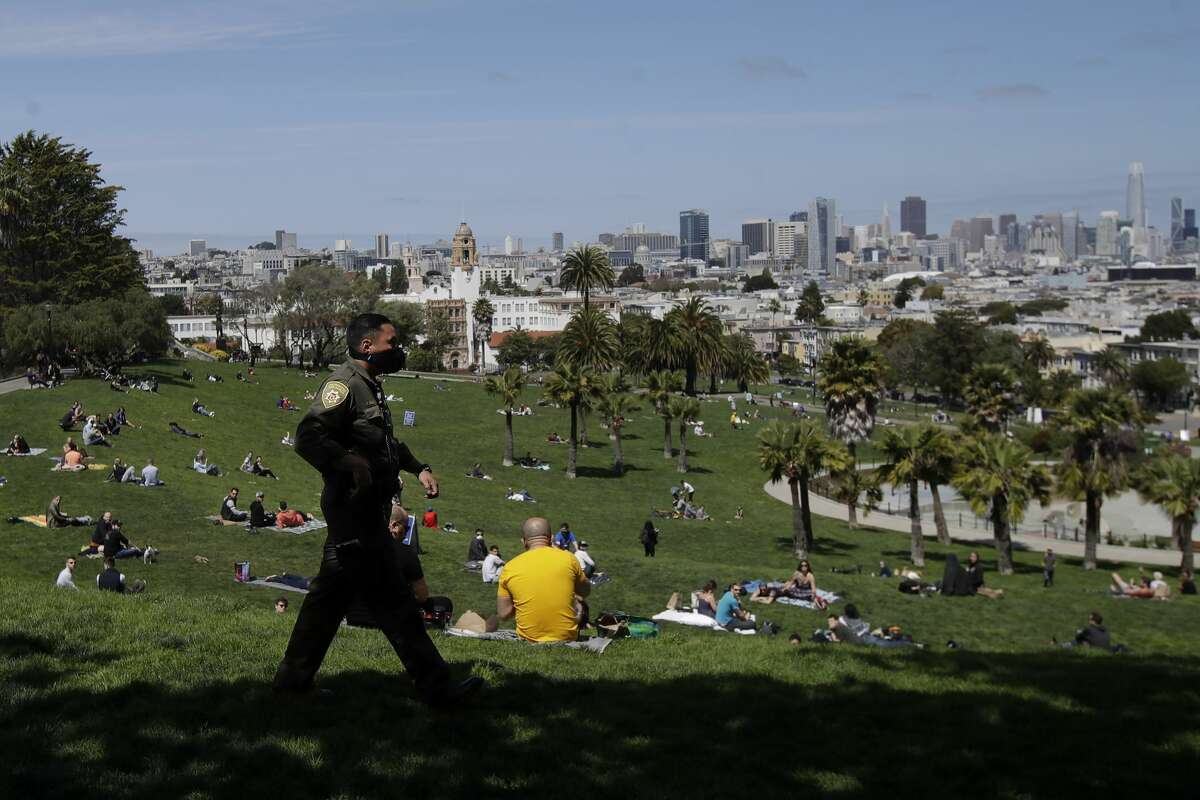 A San Francisco Park Ranger walks as people occupy a hill at Dolores Park in San Francisco, Sunday, April 19, 2020. San Francisco Police and Park Rangers reminded people who were not walking dogs, exercising or maintaining social distance to practice social distancing over COVID-19 concerns.