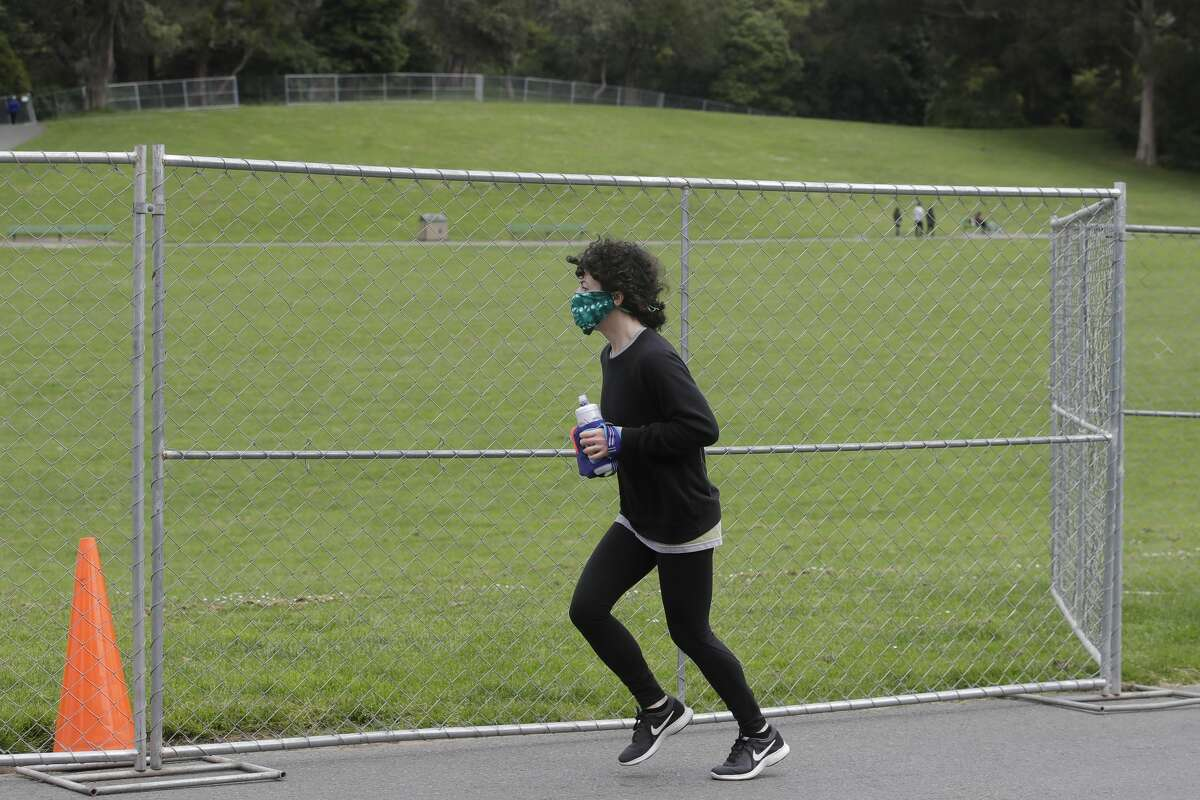 A runner jogs pass fencing to block access to Hippie Hill due to COVID-19 concerns in San Francisco's Golden Gate Park, Sunday, April 19, 2020. People annually gather on April 20, 4/20, to smoke marijuana on Hippie Hill.