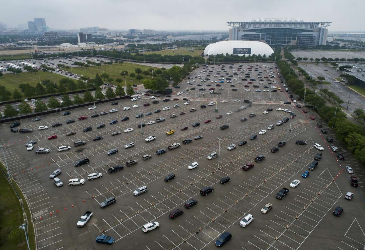 Hundreds of cars wait in line to receive food from a distribution site in one of the parking lots adjacent to NRG Stadium, Saturday, April 18, 2020, in Houston. The Houston Independent School District partnered with the Houston Food Bank to distribute what they said initially would be 3,000 bags of food.