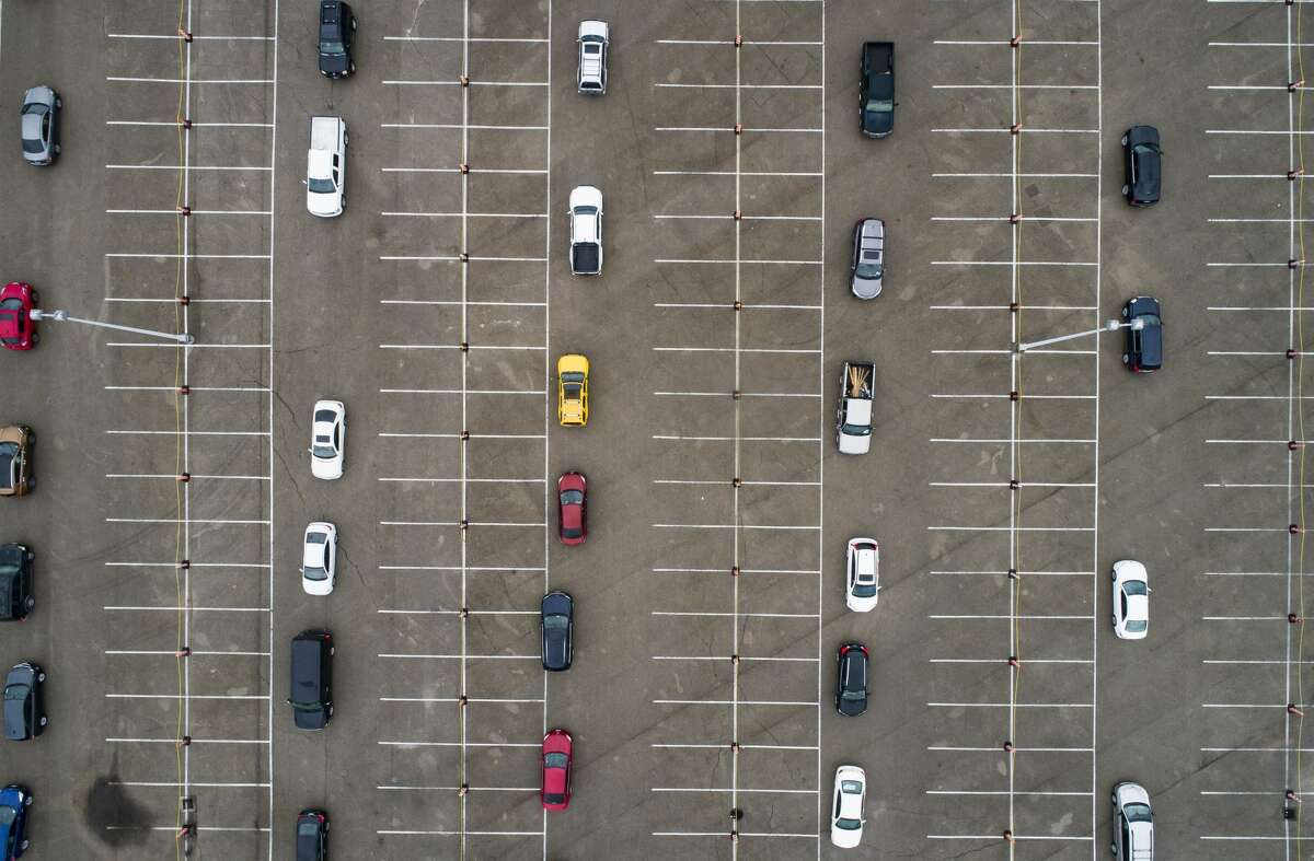 Cars wait in line to receive food from a distribution site in one of the parking lots adjacent to NRG Stadium, Saturday, April 18, 2020, in Houston. The Houston Independent School District partnered with the Houston Food Bank to distribute what they said initially would be 3,000 bags of food.