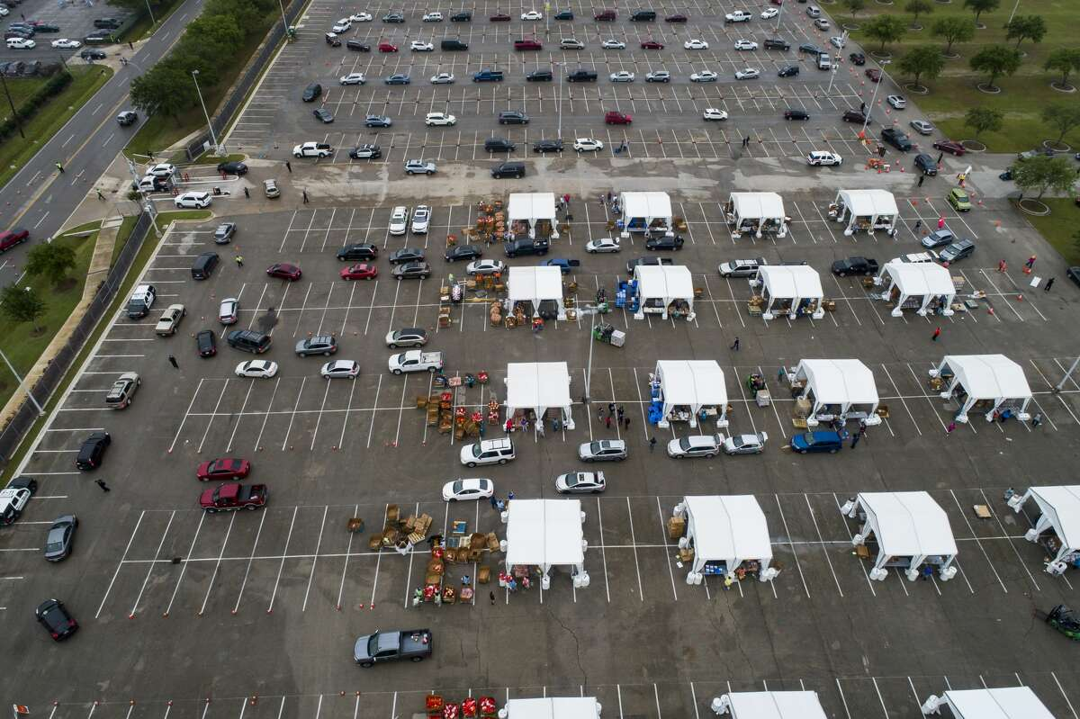 Food is distributed from tents to hundreds of cars waiting in line to receive food from a distribution site in one of the parking lots adjacent to NRG Stadium, Saturday, April 18, 2020, in Houston. The Houston Independent School District partnered with the Houston Food Bank to distribute what they said initially would be 3,000 bags of food.