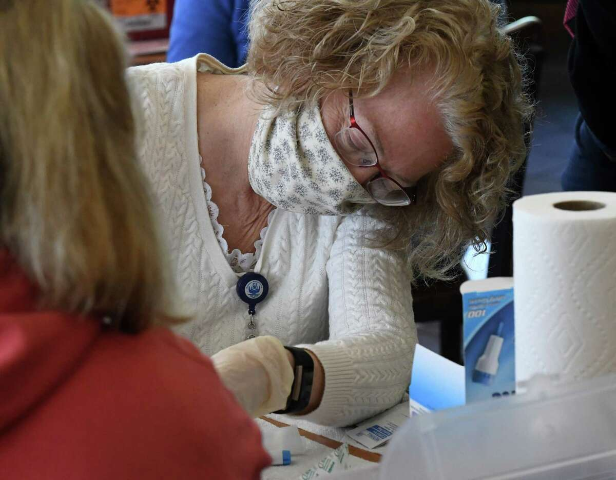 Workers with the New York State Department of Health collect blood samples to test for COVID-19 antibodies on Monday, April 20, 2020, at a supermarket on Central Avenue in Albany, N.Y. (Will Waldron/Times Union)