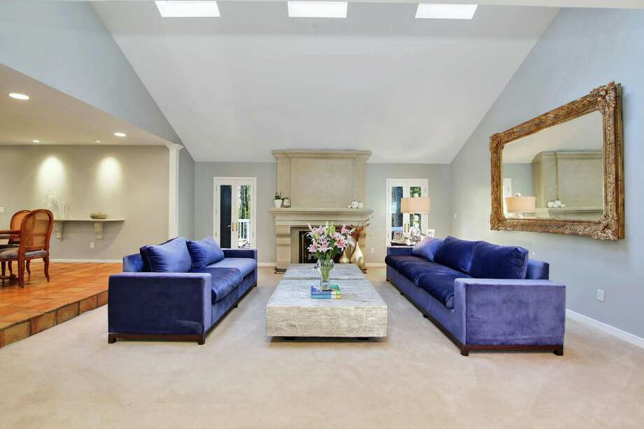 In the formal living room there is a floor to ceiling concrete fireplace flanked by French doors to the patio.