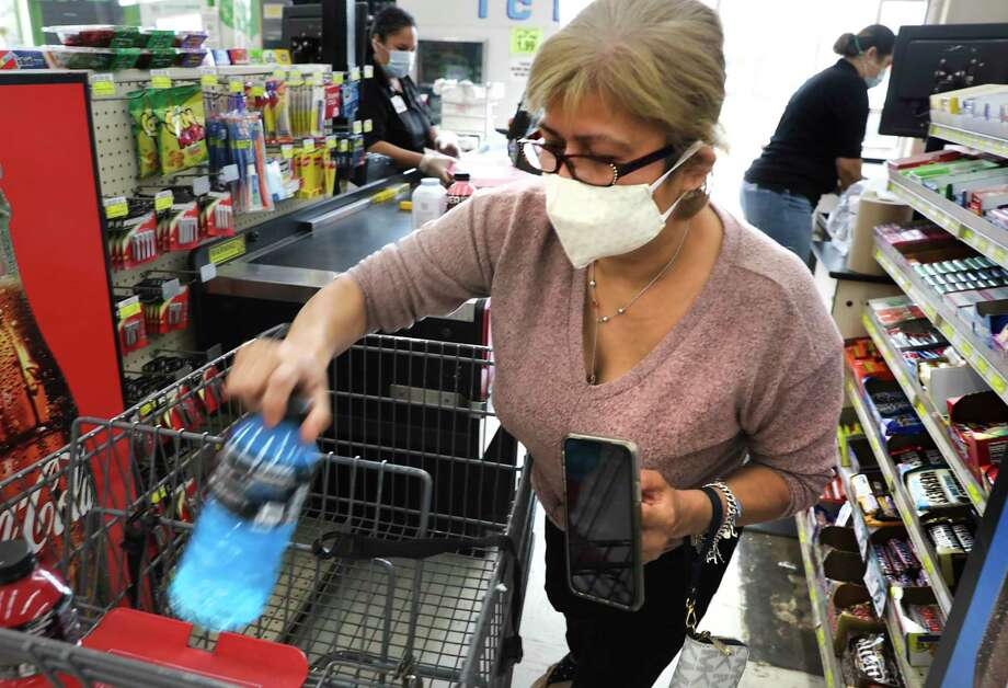 Lydia Segura, a shoppers at La Fiesta on S. Flores, wears a mask as she unloads her purchases so cashier Yvonne Acevedo, left, can check her out on April 20, 2020. Photo: Bob Owen /Staff Photographer / ©2020 San Antonio Express-News