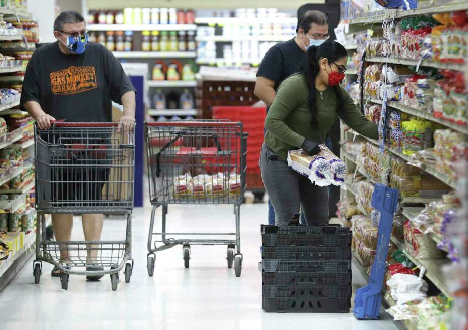 """Lupita Fuentes, right, stocks loaves of bread at La Fiesta on S. Flores, as Juan Gonzalez, left, shops, on April 20, 2020. """"I think that the worst decision that he made was to not require the mandatory use of face masks,"""" Bexar County Judge Nelson Wolff says of Abbott. Photo: Bob Owen /Staff Photographer / ©2020 San Antonio Express-News"""