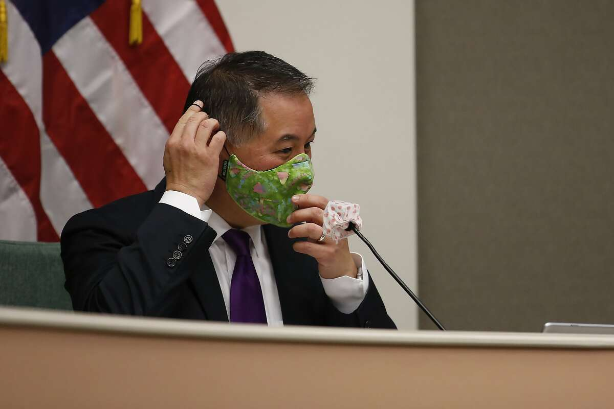 Assemblyman Phil Ting, D-San Francisco, chair of the Assembly budget committee, puts on a face mask before the start of an oversight hearing of the Assembly budget special subcommittee on COVID-19 at the Capitol in Sacramento, Calif., Monday, April 20, 2020. Lawmakers are looking into how Gov. Gavin Newsom has been spending money to address the new coronavirus crisis. (AP Photo/Rich Pedroncelli, Pool)