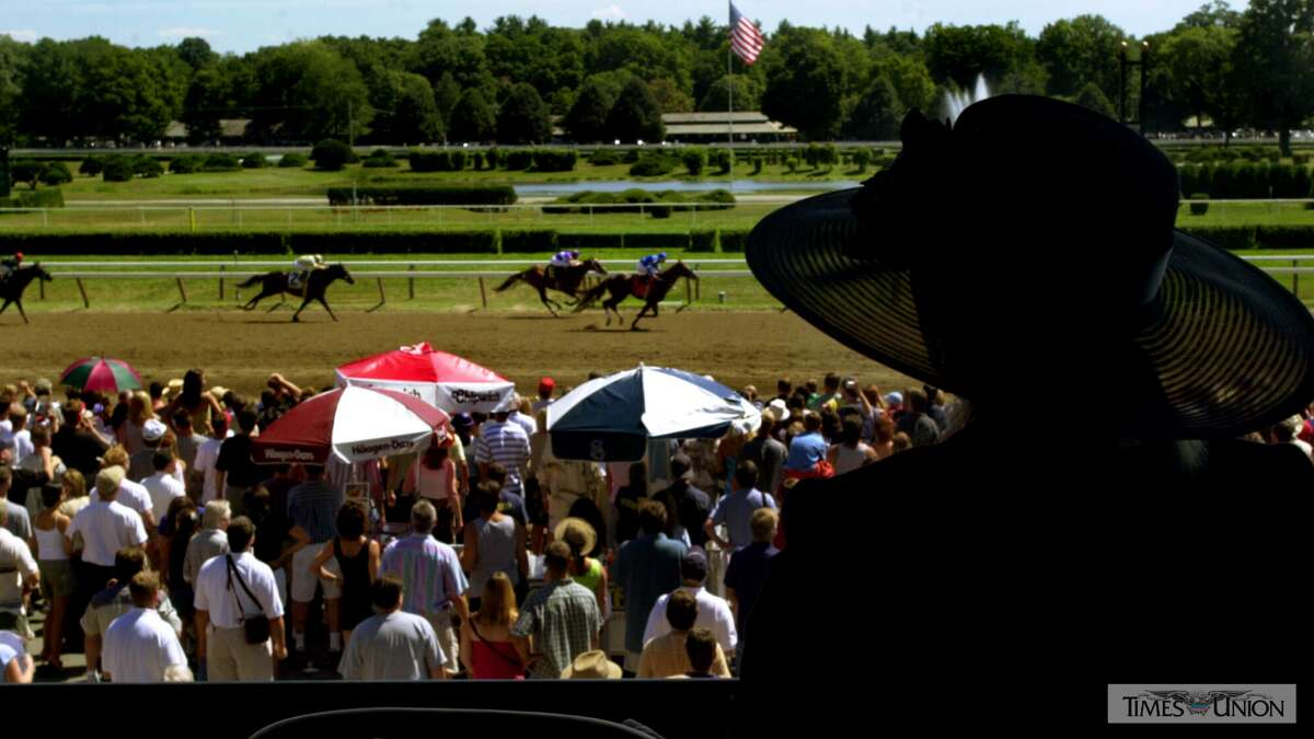 Racing fans watch the horses run the final stretch in the third race on Travers Day at the Saratoga Racecourse in 2001.Right-click to download