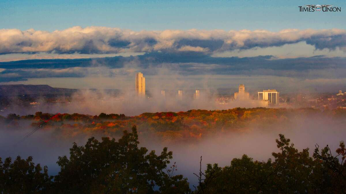 Fog settles around the buildings in Albany as the sun rises in a view from Rensselaer.Right-click to download