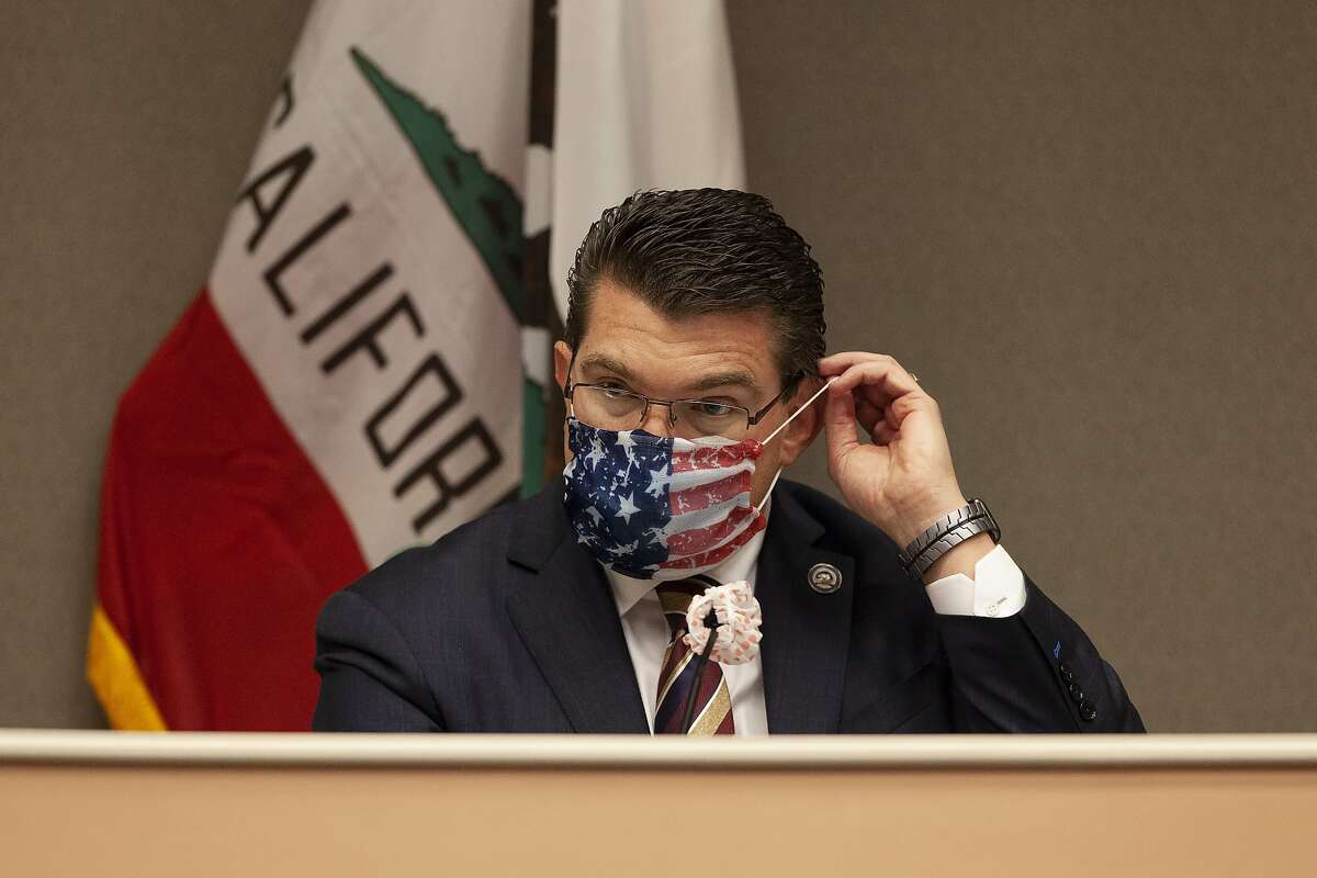 Assemblyman Jay Obernolte, R-Big Bear Lake, vice chair of the Assembly budget committee, puts on a mask before the start of an oversight hearing of the Assembly budget special subcommittee on COVID-19 at the Capitol in Sacramento, Calif., Monday, April 20, 2020. Lawmakers are looking into how California Gov. Gavin Newsom has been spending money to address the new coronavirus crisis. (AP Photo/Rich Pedroncelli, Pool)