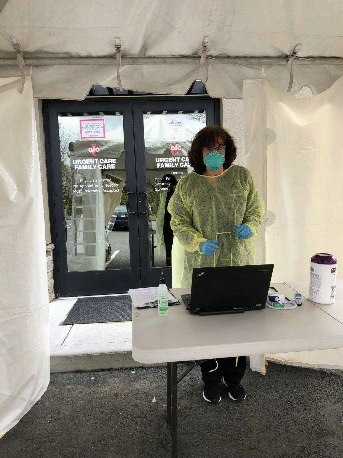 A care provider at American Family Care on East Main Street, Torrington, welcomes a patient for a COVID-19 test, which is being administered outside the facility in a small tent.