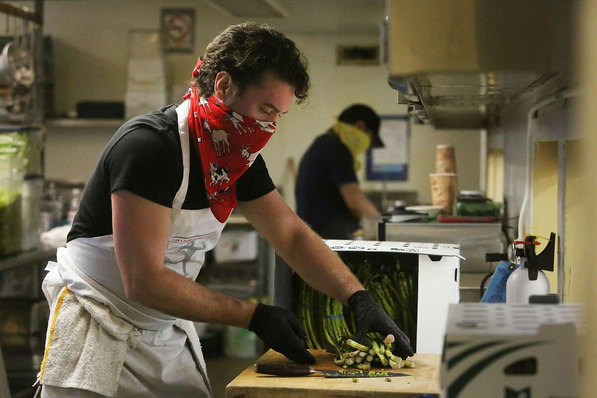 Todd Corboy, Food Runner chef, chops asparagus as he works in the new Food Runners' kitchen with members of the chef team at the Waller Center on Monday, April 20, 2020 in San Francisco, Calif.