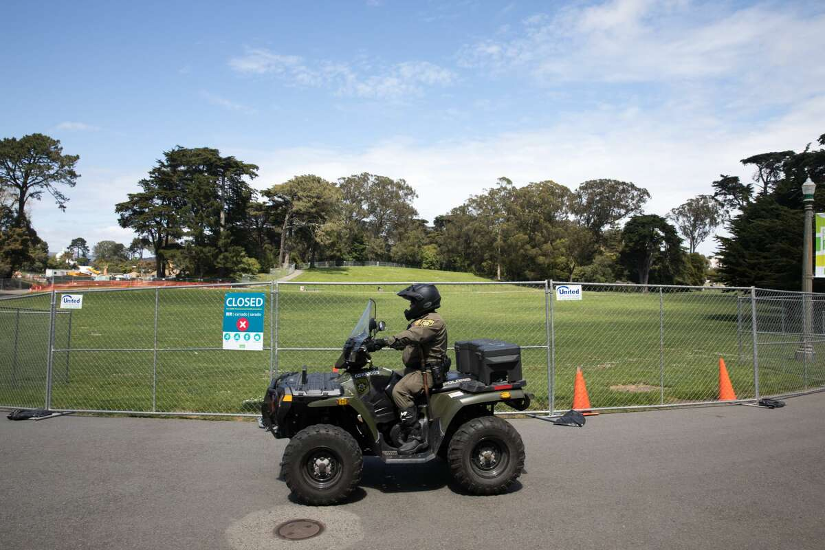 A San Francisco Park ranger patrols outside the fence that cordoned off Hippie Hill in Golden Gate Park. The area was fenced off and patrolled by San Francisco Police Officers, Sheriff's and Park Rangers.