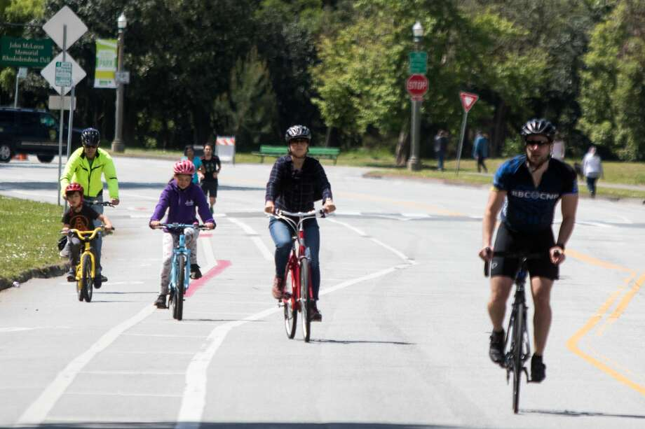 Pedestrians and bicyclists enjoy riding on a closed off section of JFK Drive in Golden Gate Park. Several roads were closed around Hippie Hill in Golden Gate Park. The area was also fenced off and patrolled by San Francisco Police Officers, Sheriff's and Park Rangers. Due to the COVID-19 coronavirus restrictions on public gatherings, the annual 4/20 celebration at Golden Gate Park Hippie Hill was canceled on April 20, 2020. Photo: Douglas Zimmerman/SFGate / SFGate