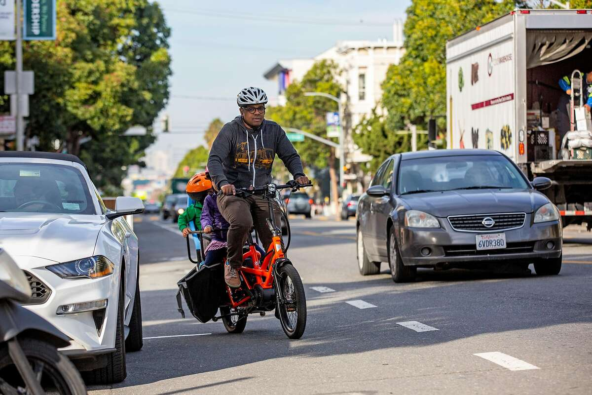 Ed Parillon with his children ride a bike in the Mission District, Friday, Jan. 3, 2020, in San Francisco, Calif. Parillon runs errands and uses a bike instead of a car.