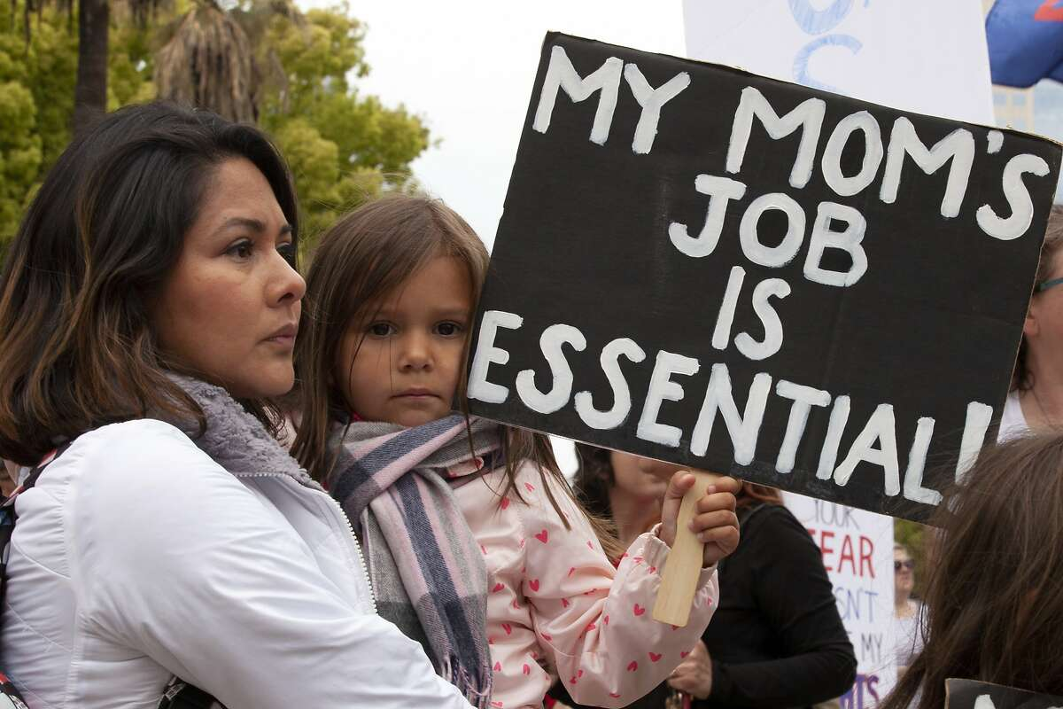 Georgina Orante, holds her daughter, Sophie, 4, at a rally calling for the end of Gov Gavin Newsom's stay-at-home orders, in Sacramento, Calif., Monday, April 20, 2020. Several hundred people gathered at the Capitol demanding that Newsom ease the restrictions and allow people return to work. Orante owns a hair salon in Southern California and says she will lose her business if she can not go back to work. (AP Photo/Rich Pedroncelli) i