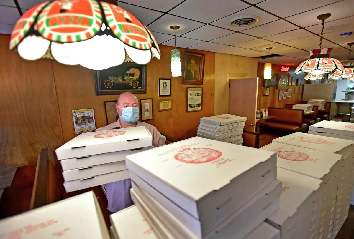 Ole Knudsen, Sally's Apizza general manager, stacks empty pizza boxes Monday to be used for delivery from the New Haven pizzeria.