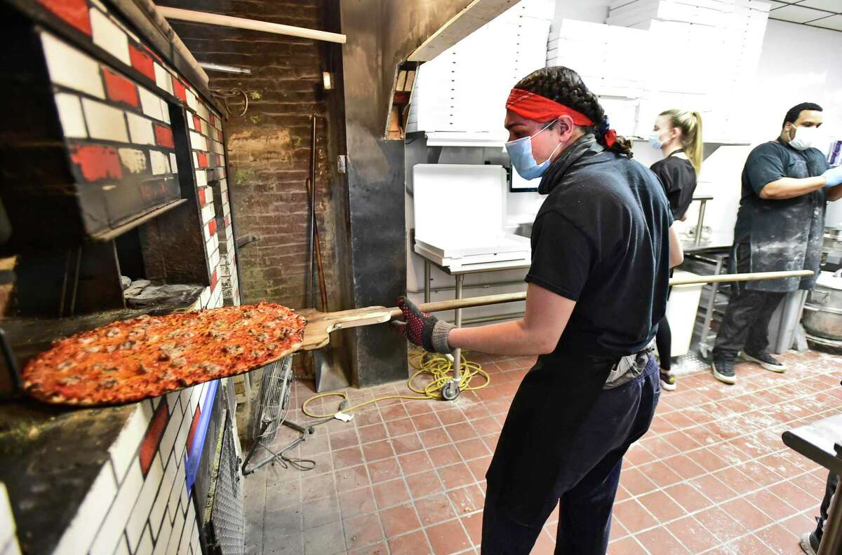 Brian Rodriguez, Sally's Apizza's baker moves a pizza around the coal-fired oven at the New Haven pizzeria in April.