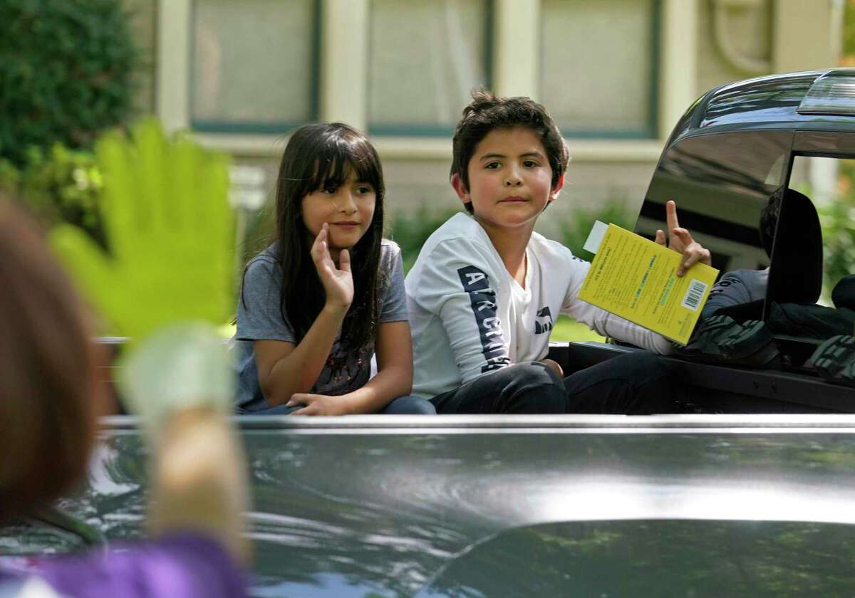 Camila Rios, a second grader, left, and her brother, Niko Rios, a fifth grader, wave after picking up their books for the One Book, One School shared reading event Thursday at Houston ISD's Travis Elementary School. Students in HISD might return to school earlier in August or see a longer class day in 2020-21 to make up for lost instructional time due to the novel coronavirus pandemic.