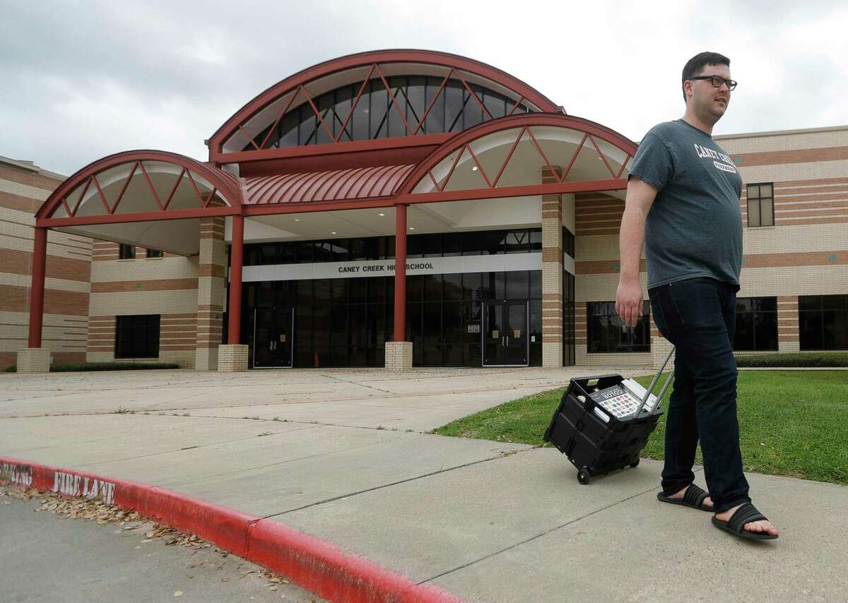 In this March photo, Caney Creek High School yearbook teacher Stephen Green wheels books to his car as he prepares to work for Conroe ISD from home. School districts across Houston are making contingency plans for when in-person classes might resume in 2020-21, which will largely depend on public health concerns tied to the novel coronavirus pandemic.