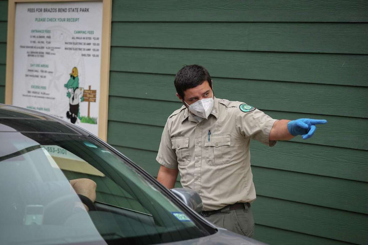 Customer Service Representative Matthew Argo wears a mask and gloves as he greets visitors after Gov. Greg Abbott signed an executive order to open state parks like Brazos Bend State Park Monday, April 20, 2020, in Needville. The Governor's executive order, park visitors will be required to wear face masks and maintain social distancing guidelines, with family groups no larger than five people. Anyone wishing to visit the parks need to fill out an online reservation prior to being admitted.
