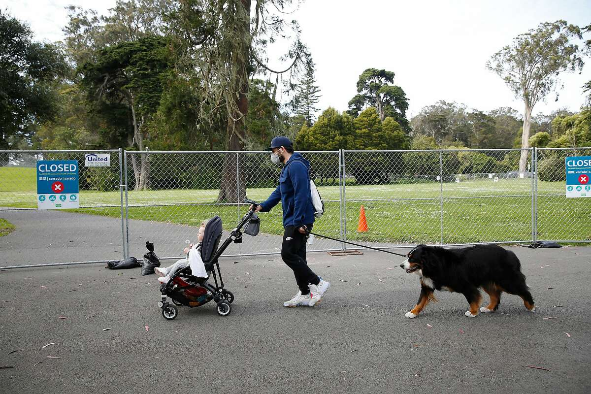 Amit (center) pushes daughter Nina, 1, in a stroller as he holds Patty on a leash as they walk past a fence surrounding a closed Robin Williams Meadow and Hippie Hill area in Golden Gate Park which was closed for Covid-19 health precautions on 420 day on Monday, April 20, 2020 in San Francisco, Calif. The trio were getting an outing during the Covid-19 shutdown.