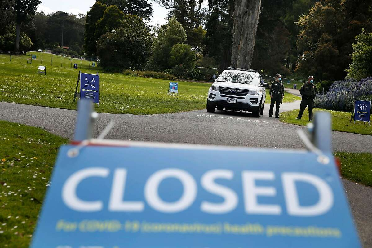 Park rangers stand next to a vehicle blocking a path on 420 day as they stand next to the closed and fenced in area around Robin Williams Meadow and Hippie Hill in Golden Gate Park on 420 day on Monday, April 20, 2020 in San Francisco, Calif.