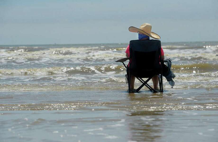 Amber Byford, a hairdresser from Dayton who is not working after her salon was closed, wears her bandana as she sits amid the surf at Sea Rim State Park Monday, which was the first day state parks reopened after being closed due to COVID-19. The park required online reservations and payment to reduce interaction paying at the gate, and also said visitors needed to observe social distancing and have face masks to wear while on the grounds.   Photo taken Monday, April 20, 2020 Kim Brent/The Enterprise Photo: Kim Brent / The Enterprise / BEN