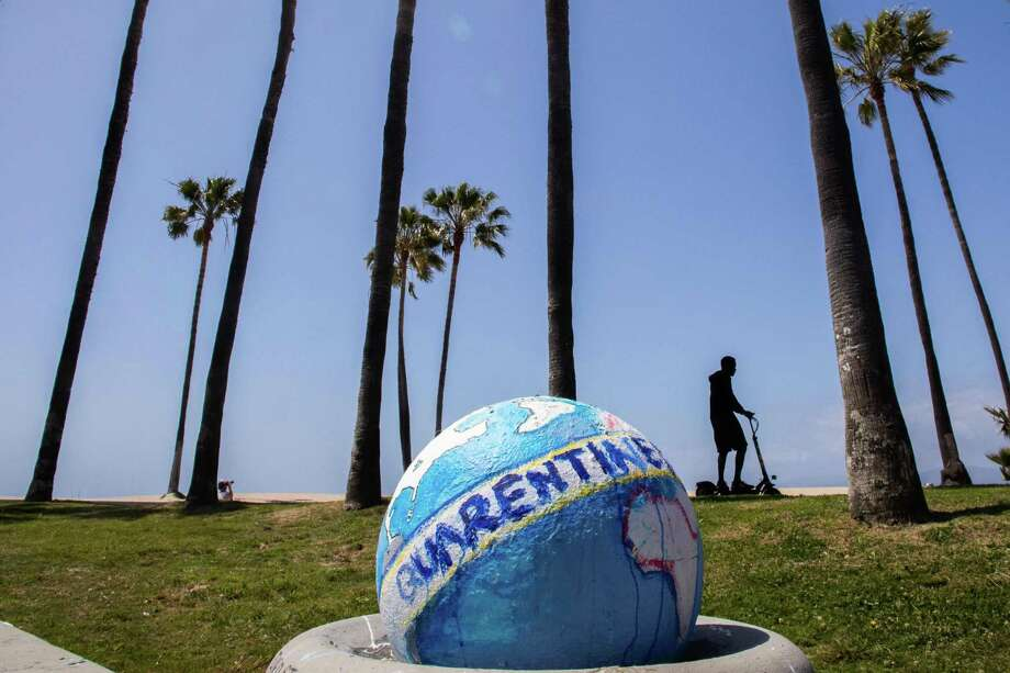 A man rides his scooter past a sculpture of a quarantined earth in Venice Beach earlier this month. With the nation in quarantine, the U.S. could be learning valuable environmental lessons for the future. Photo: APU GOMES /AFP Via Getty Images / AFP or licensors