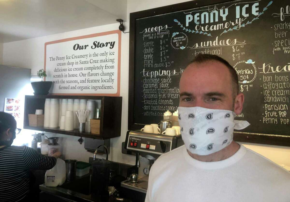 """In this April 17, 2020, photo, Zachary Davis poses for a photo at The Penny Ice Creamery in Santa Cruz, Calif. An investigation by The Associated Press hows that many large companies which collectively received tens of millions of dollars in federal loans through the Paycheck Protection Program were at risk of failing even before the coronavirus walloped the economy, while others have acknowledged problems keeping their finances straight and a few have been under investigation by the Securities and Exchange Commission. That big companies and ones with questionable records received such precious financial aid during the chaotic last few weeks frustrates Davis, """"We were feeling pretty good about where we were in the world. Now it's just all turned upside down,"""" said Davis, who had to lay off 70 workers."""