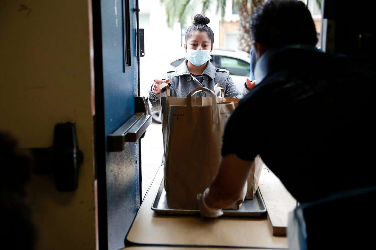 Jorge Mancera (right), San Francisco Unified School District, Galileo High School Student Nutrition Services lead manager, passes bags filled with meals to Leslie Mejia, 16, Mission High School junior, during a SFUSD school meal pickup at Mission High School on Monday, April 20, 2020 in San Francisco, Calif.