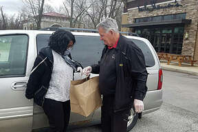 Mike Shannon, the owner of Mike Shannon's Grill in Edwardsville, delivers kids' meal to a customer in the parking lot shortly after the restaurant switched to curbside delivery due to the COVID-19 pandemic.