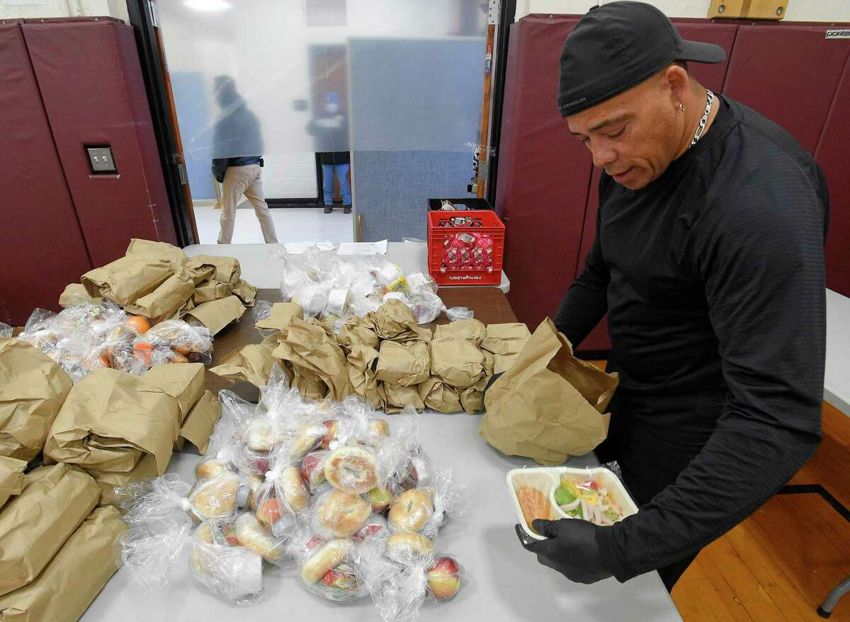 Volunteer P.J. Johns checks the contents of a meal that is being handed out to families on Friday, April 17, 2020 in Stamford, Connecticut. As part of the Grab and Go Meals that Stamford Schools is providing to families, Johns, a resident of Darien is volunteering with a Norwalk based non profit Filling in the Blanks, helping supplement Stamford Schools Grab and Go Meal plan, ensuring no child goes hungry while schools are closed. Over 500 volunteers have partnered with the City of Stamford's citywide Stamford Together program to help support emergency response efforts related to the COVID-19 public health emergency. Volunteers step up to help in food distribution, testing site check in's and other areas throughout the city and Fairfield County.