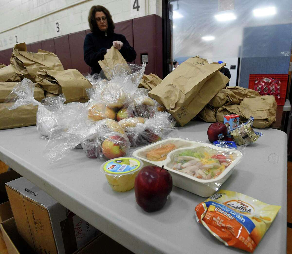 Volunteer Connie Begetis of Stamford bags up meals that are being distributed to families on Friday, April 17, 2020 in Stamford, Connecticut. The Grab and Go Meals plan that Stamford Schools is providing to families, ensures no child goes hungry while schools are closed. Over 500 volunteers have partnered with the City of Stamford's citywide Stamford Together program to help support emergency response efforts related to the COVID-19 public health emergency. Volunteers step up to help in food distribution, testing site check in's and other areas throughout the city and Fairfield County.