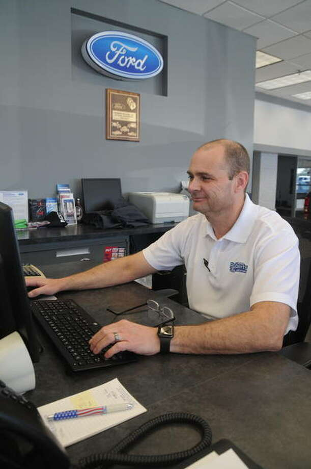 John Roberts, general manager of Roberts Motors of Alton, accesses the internet at the dealership. Roberts Motors is offering area students free parking lot access to the dealership's WiFi service.