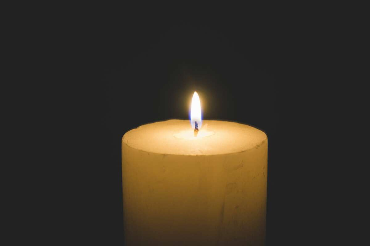 A small candle burns in the dark