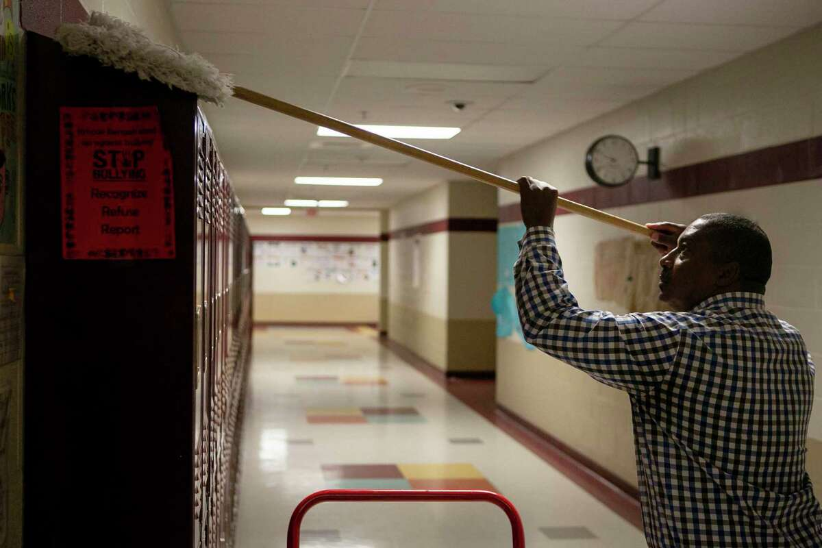 Northside ISD custodial supervisor Kenneth Timbers cleans lockers during Spring Break at Dolph Briscoe Middle School. Days later, schools were closed in response to the coronavirus pandemic, and have not reopened. The economic damage to the state has school superintendents worried about serious funding cuts as they try to plan budgets for next school year.