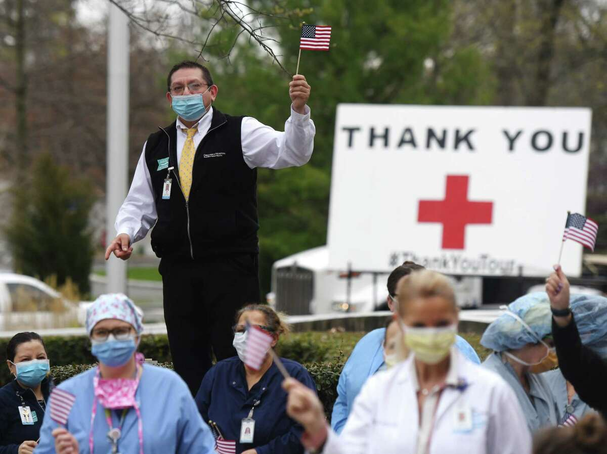 Rick Auz, of Greenwich Hospital patient relations, waves a flag with other hospital employees outside Greenwich Hospital in Greenwich, Conn. Tuesday, April 21, 2020. K & J Tree Service stopped at Greenwich Hospital Tuesday as part of its