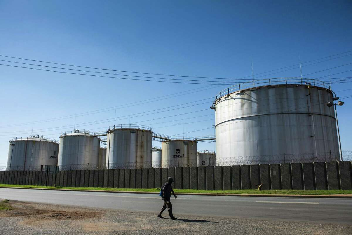 A pedestrian walks alongside oil storage tanks at a facility in the Alrode district of Johannesburg, South Africa, on Tuesday, April 21, 2020. The oil meltdown accelerated, with huge losses sweeping through markets as the world runs out of places to store unwanted crude and grapples with negative pricing. Photographer: Waldo Swiegers/Bloomberg
