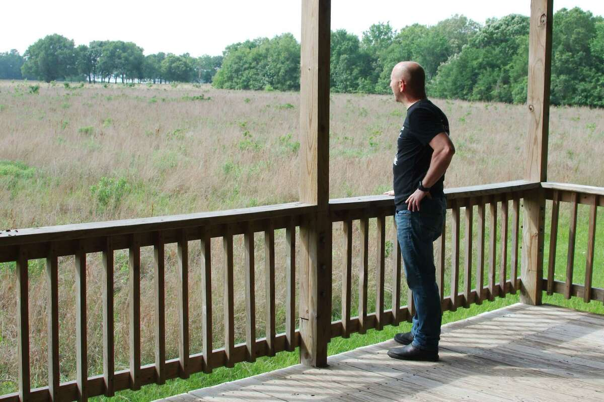 Armand Bayou Nature Center Executive Director Tim Pylate looks out over a silent expanse of natural coastal prairie grassland that runs along the bayou at the center, which has been closed since mid-March because of the novel coronavirus pandemic. The center hopes to open May 1 but will adhere to state and local guidelines, Pylate said.