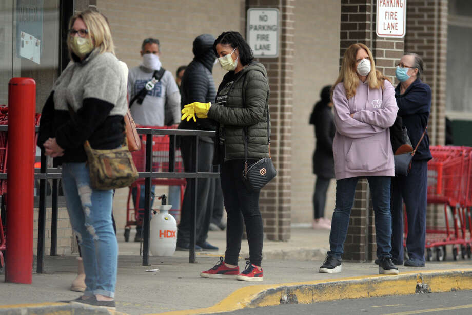 Shoppers line up outside Trader Joe's, in Milford, Conn. April 21, 2020. Face coverings were widely in use Tuesday by customers and workers across the state, less than 24 hours after the implementation of Gov. Ned Lamont's order directing masks to be worn in public settings where social distancing is not possible. Photo: Ned Gerard, Hearst Connecticut Media / Connecticut Post