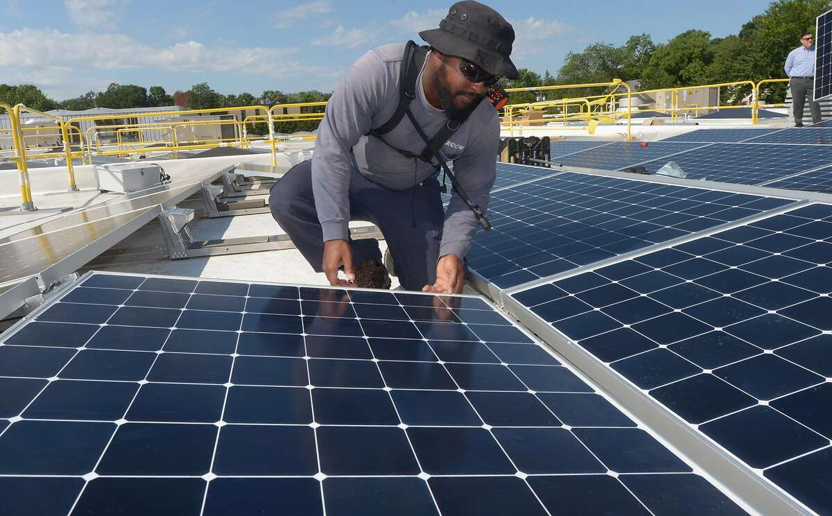 ENCON employee Andrew Richards installs solar panels on the roof of the Paul Miller Nissan dealership in Fairfield, which has installed the solar-energy array with financing from Darien-based Greenworks Lending, Wednesday, July 18, 2018, in Fairfield, Conn.