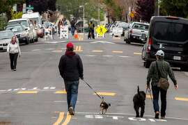 People along the closed 42nd Street off Broadway on Saturday, April 11, 2020, in Oakland, Calif. Mayor Libby Schaaf ordered approximately 10% of Oakland streets too close. It�s about 74 miles of roadway. The purpose is for people to walk, jog or ride bicycles during the shelter-in-place period. The closures are happening in phases. Crews will put temporary plastic barriers on the first batch of streets Saturday, allowing enough space for people who live on the affected streets to drive to and from their homes.