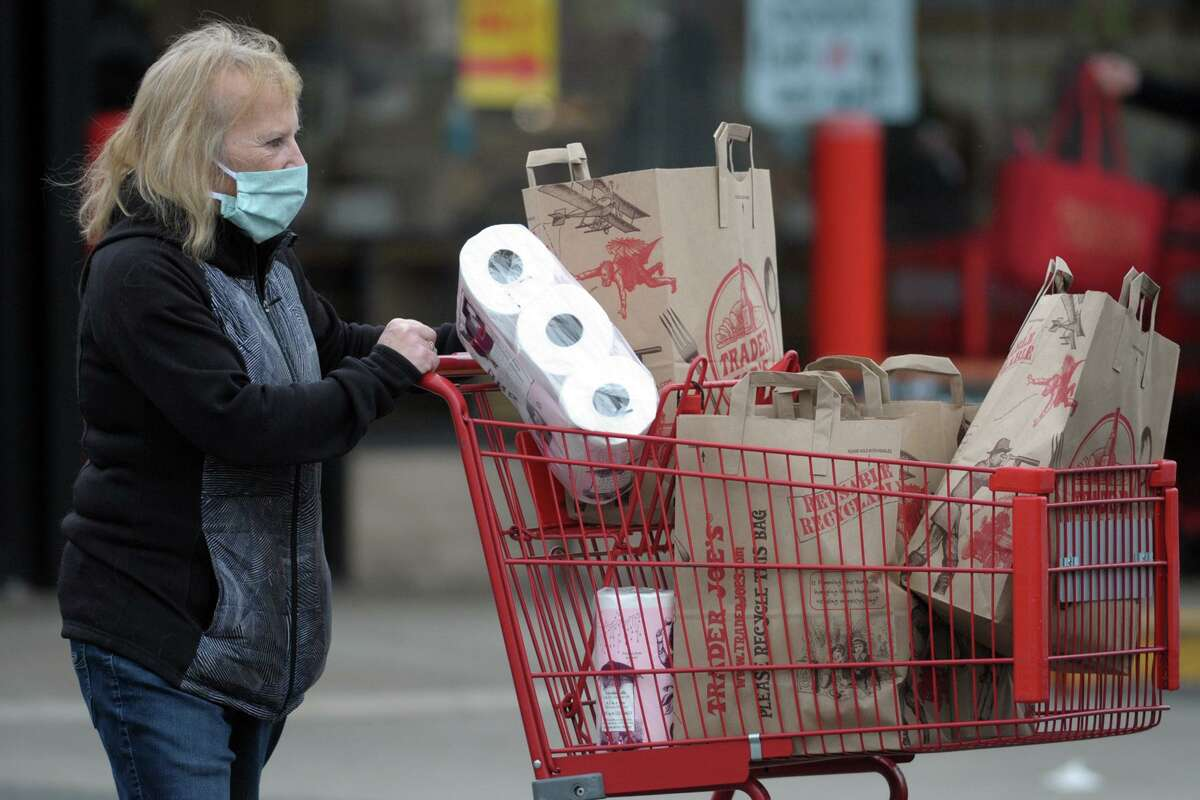 A shopper exits Trader Joe's, in Orange, Conn. April 21, 2020. In a recent episode of its podcast, Trader Joe's explained why it hasn't added curbside pickup or delivery to its store offerings during the coronavirus pandemic.