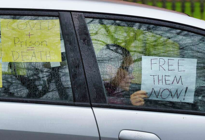 A protestor holds a sign inside a vehicle as advocates calling for the release of medically vulnerable prisoners because of the pandemic, held a protest outside the New York State Executive Mansion on Tuesday, April 21, 2020, in Albany, N.Y. (Paul Buckowski/Times Union)