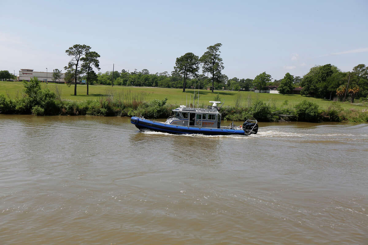 A Harris County Sheriff's boat heads downstream while the Coast Guard is searching for seven possible people in the water in Cedar Bayou just west of the U.S. Highway 146 bridge Tuesday, April 21, 2020, in Baytown.