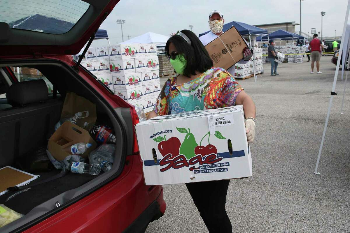 Claudia Uresti, 53, loads a box of apples into the trunk of a vehicle during a San Antonio Food Bank mega distribution event at NISD Hardin Athletic Complex, Tuesday, April 21, 2020. They were expecting to serve 2,600 households.