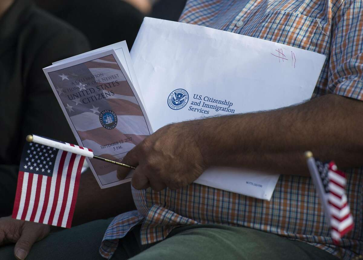 """(FILES) In this file photo taken on September 12, 2017 a new US citizen holds an information packet at a naturalization ceremony at Alexandria City Hall in Alexandria, Virginia. - US President Donald Trump said in a Tweet on April 20, 2020 that he will sign an executive order to """"temporarily suspend immigration into the United States"""", amid the novel coronavirus pandemic. (Photo by ANDREW CABALLERO-REYNOLDS / AFP) (Photo by ANDREW CABALLERO-REYNOLDS/AFP via Getty Images)"""