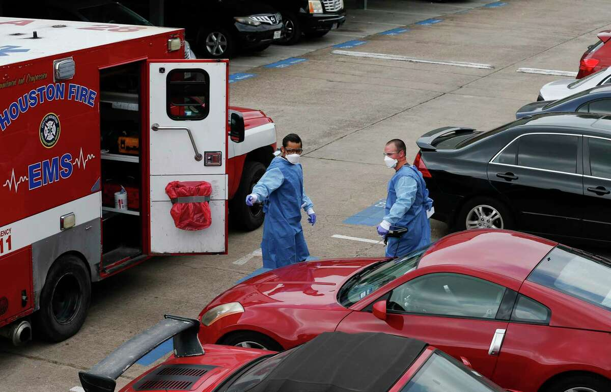 Houston Fire Department paramedics Obed Ceballos, left, and Michael Hinks, right, get ready to transport a man suspected of having COVID-19 to a hospital Wednesday, April 8, 2020, in Houston.