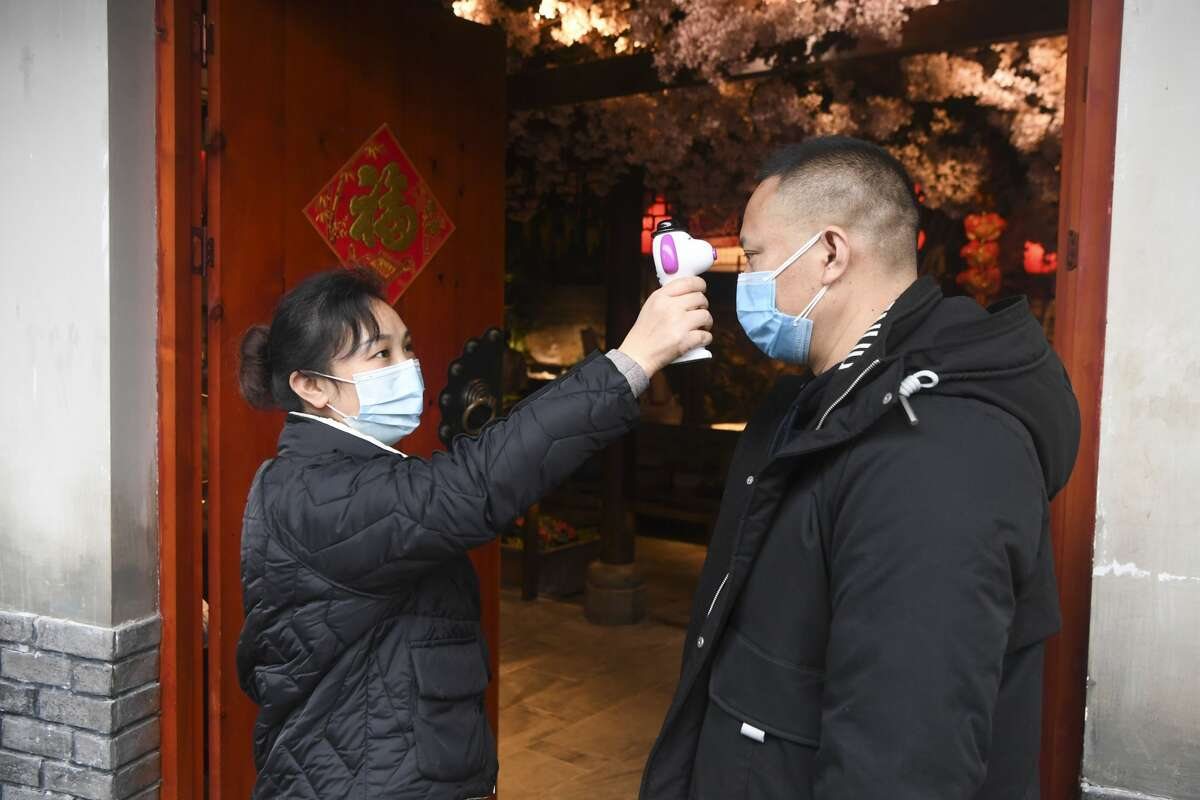 Temperature checks are also required for employees at restaurants. Shown: A staff member of a hot-pot restaurant undergoes a temperature check in southwest China's Chongqing Municipality on Feb. 15, 2020.